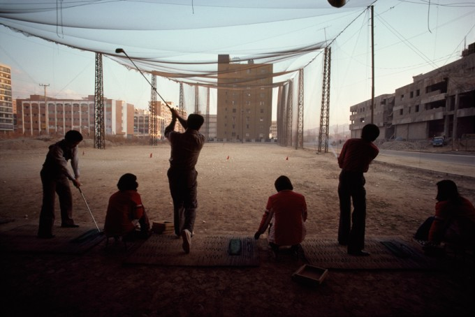 A temporary vacant lot serves as driving range amid high rise buildings, December 1979.