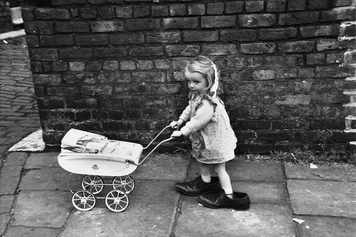 Little girl with toy pram in large shoes - Manchester 1966