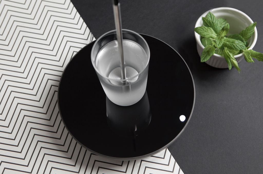 A glass cup with rod placed on a black plate in the kitchen