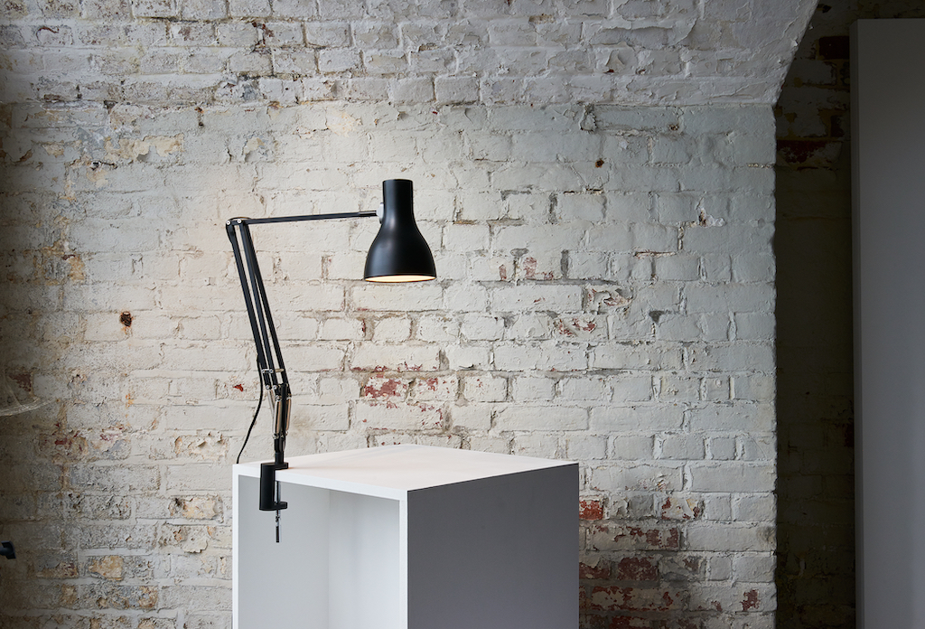 black lamp clamped onto white desk and brick wall in the background