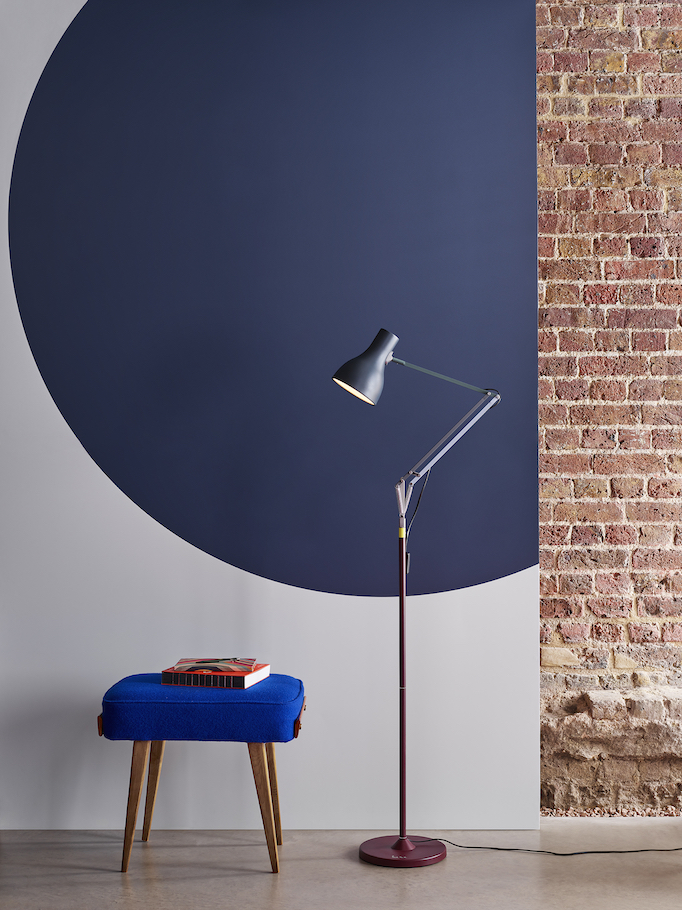 Blue and burgundy Paul Smith floor lamp in front of a brick and painted wall.